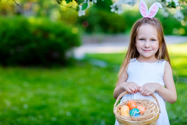 a young girl with easter bunny ears on and holding a basket.