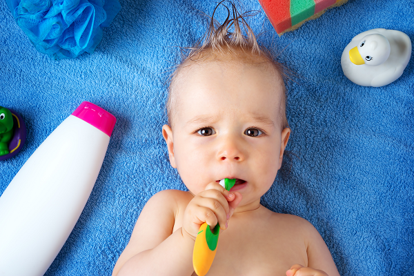 a baby holding a toothbrush in his mouth.