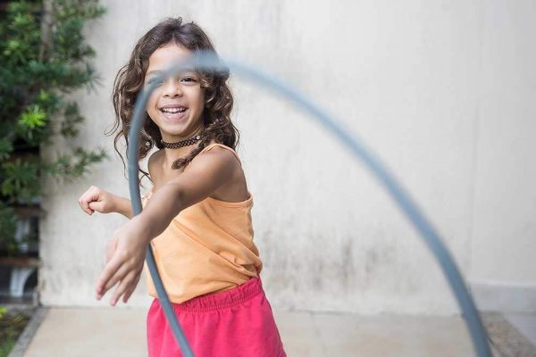 a young girl playing outside and laughing.
