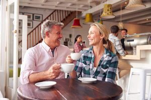 couple drinking coffee and smiling at each other