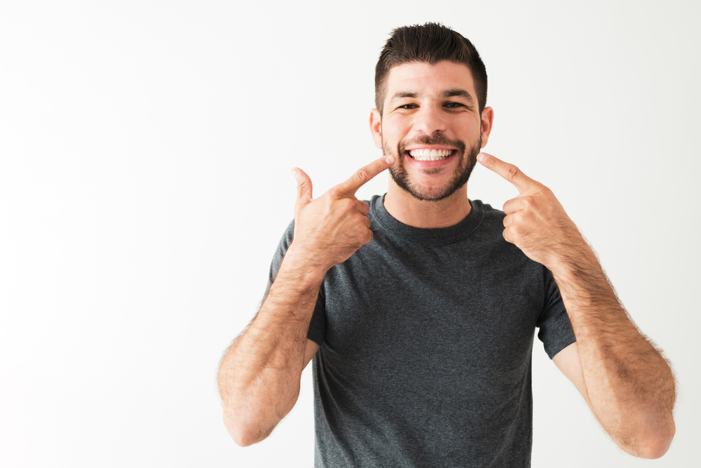 A man pointing to the results of his dental bonding procedure. His teeth are white and bright.